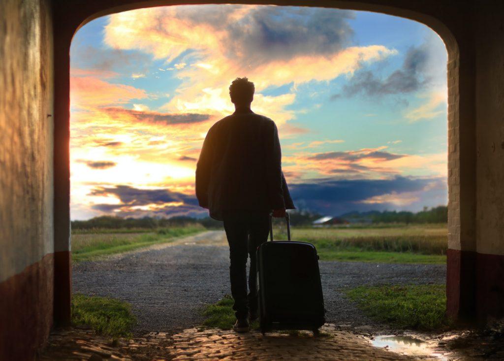 homme avec une valise avec fond couché de soleil